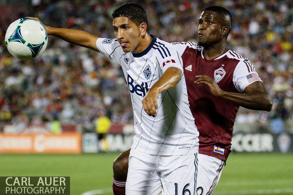 August 17th, 2013 - Vancouver Whitecaps FC defender Johnny Leveron (16) tries to keep the ball away from Colorado Rapids forward Edson Buddle (9) in the second half of action in the Major League Soccer match between the Vancouver Whitecaps FC and the Colorado Rapids at Dick's Sporting Goods Park in Commerce City, CO
