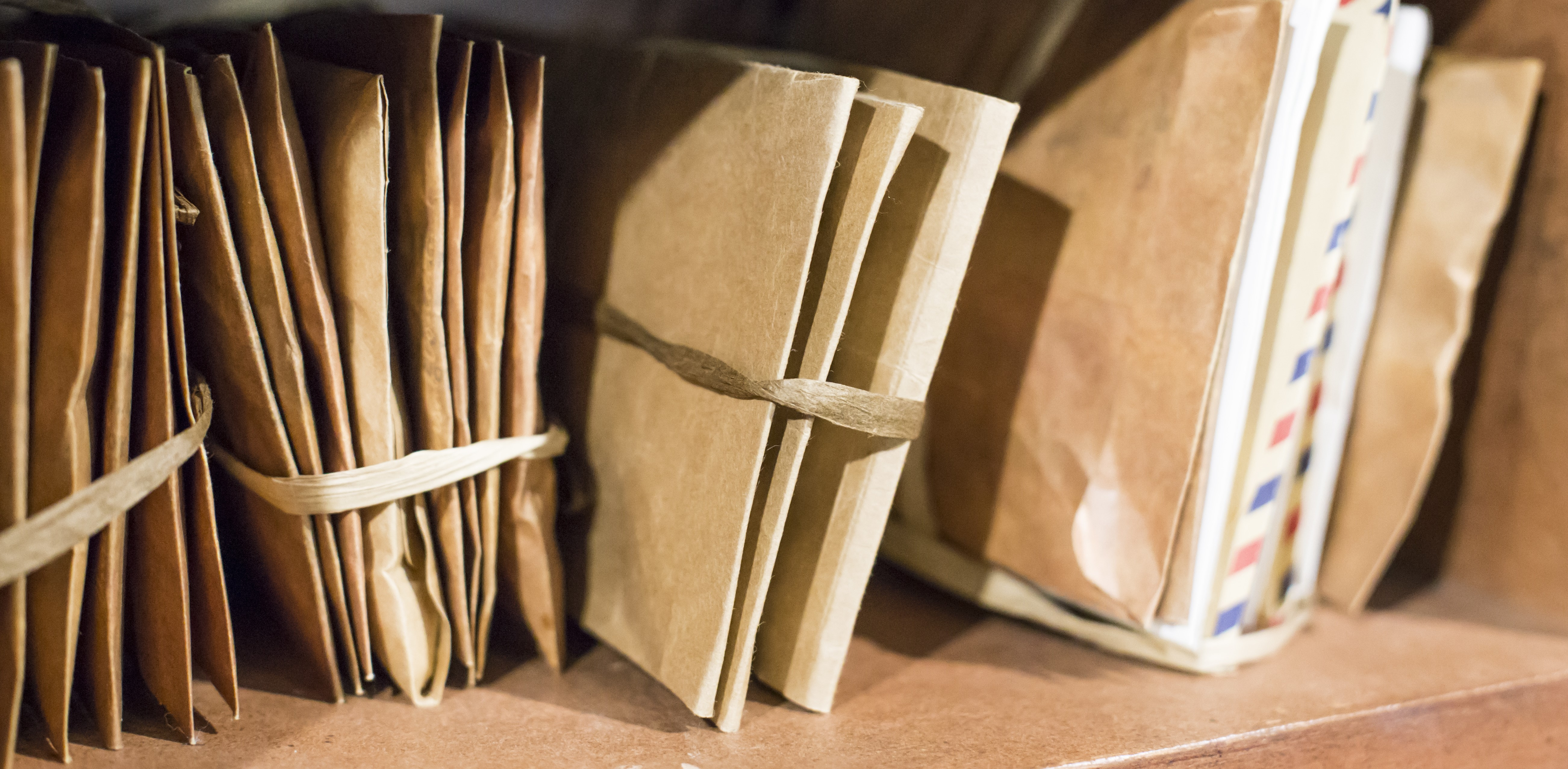 Stack of old letters on a wooden bookcase. Old mail of the post office