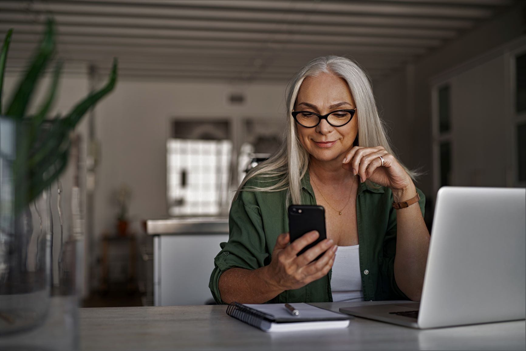 A woman looking at a mobile phone and a laptop.