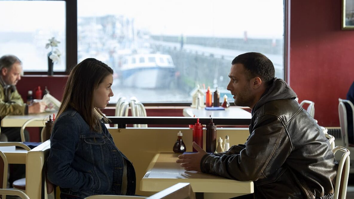 A man in his 30s at a diner table talking to a teenage girl