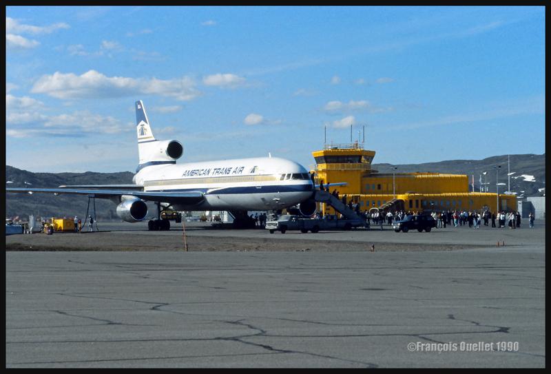 Un Lockheed L-1011 de American Trans Air stationné devant la tour de la station d'information de vol de Iqaluit (Iqaluit FSS) en 1990