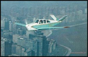 Beechcraft N35 Bonanza N545T volant au-dessus de Chicago durant les années où régnait la famille Daley (sur carte postale aviation)