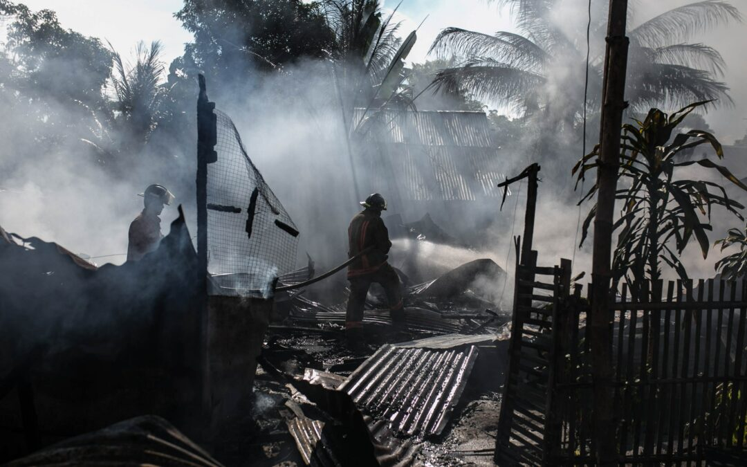 Firefighters in a burnt down building