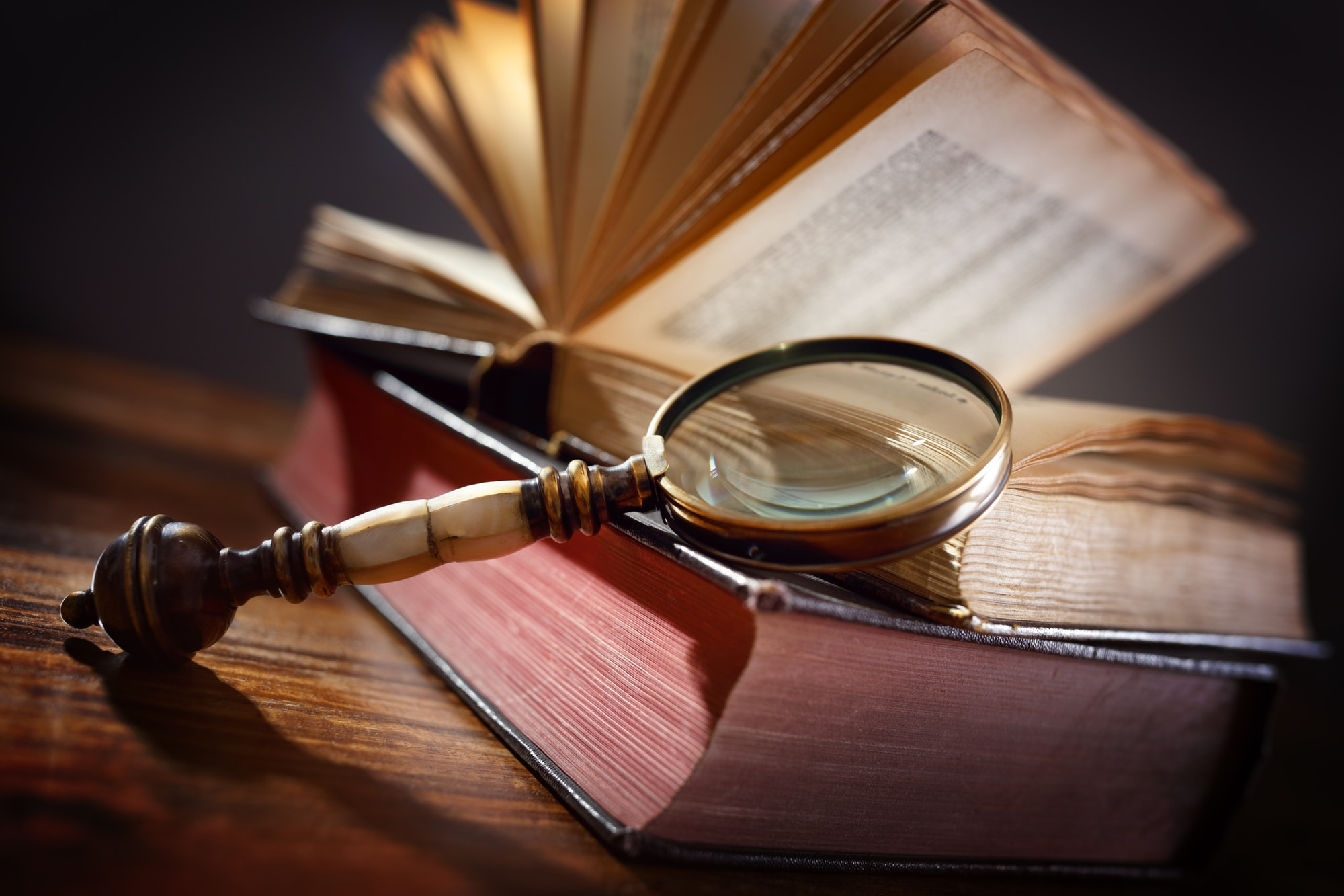 Old book and magnifying glass fla contract law legal assistance balance boca raton fl