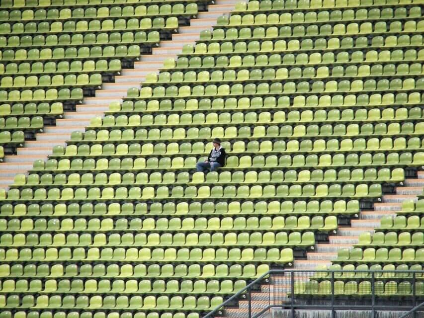 woman-in-grey-shirt-sitting-on-stadium-chair-67836