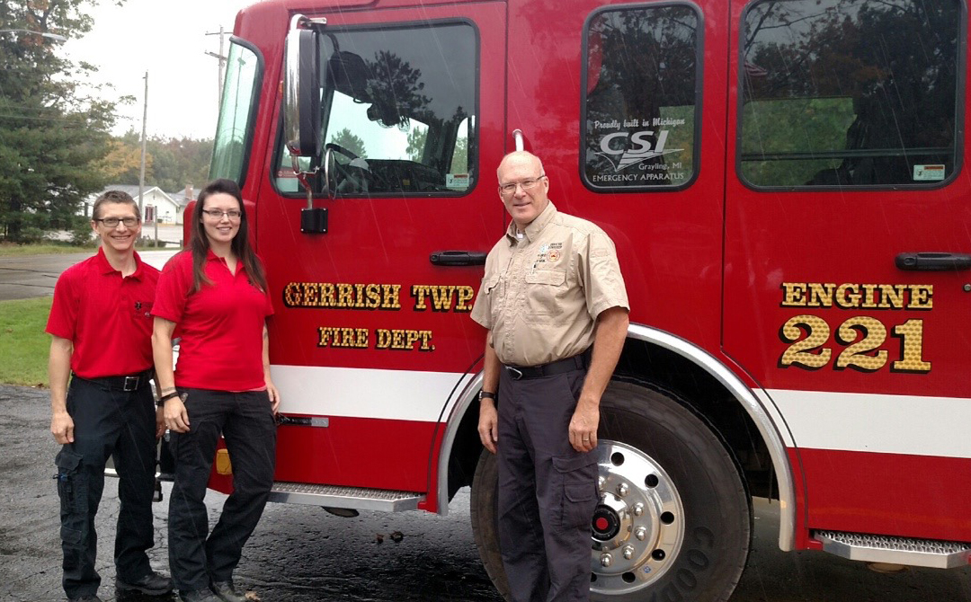 Chief Jim Fisher, Assistant Chief Brandon Rodgers and a Gerrish Township firefighter posing in front of a Gerrish fire engine.