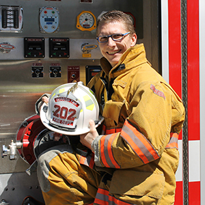 Assistant Fire Chief, Brandon Rodgers, posing in front of a Gerrish Township fire engine in his bunker gear and holding his helmet.