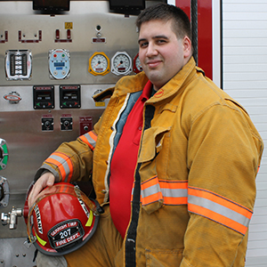 2nd Lieutenant Jason Budzinski posing in front of a Gerrish Township fire engine in his bunker gear.