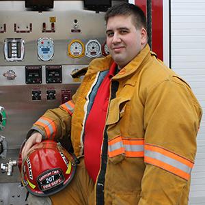 2nd Lieutenant Jason Budzinski posing in front of a Gerrish Township fire engine in his bunker gear.