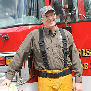 Fire Chief Jim Fisher posing in front of a Gerrish Township fire engine in his bunker gear.