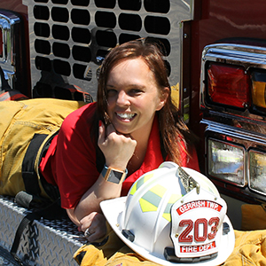Kristi Gilliam posing on a Gerrish Township fire engine in her bunker gear.