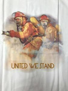 "Close-up of white ""United We Stand"" t-shirt with image of two firefighters on the back."