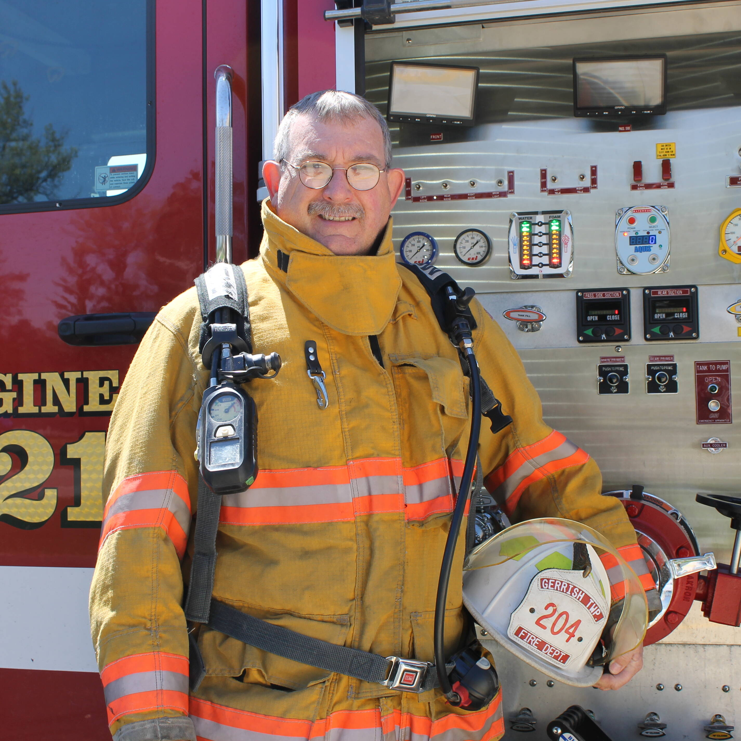 Jake Figley posing on the side of a Gerrish Fire Engine with a helmet tucked under his arm.