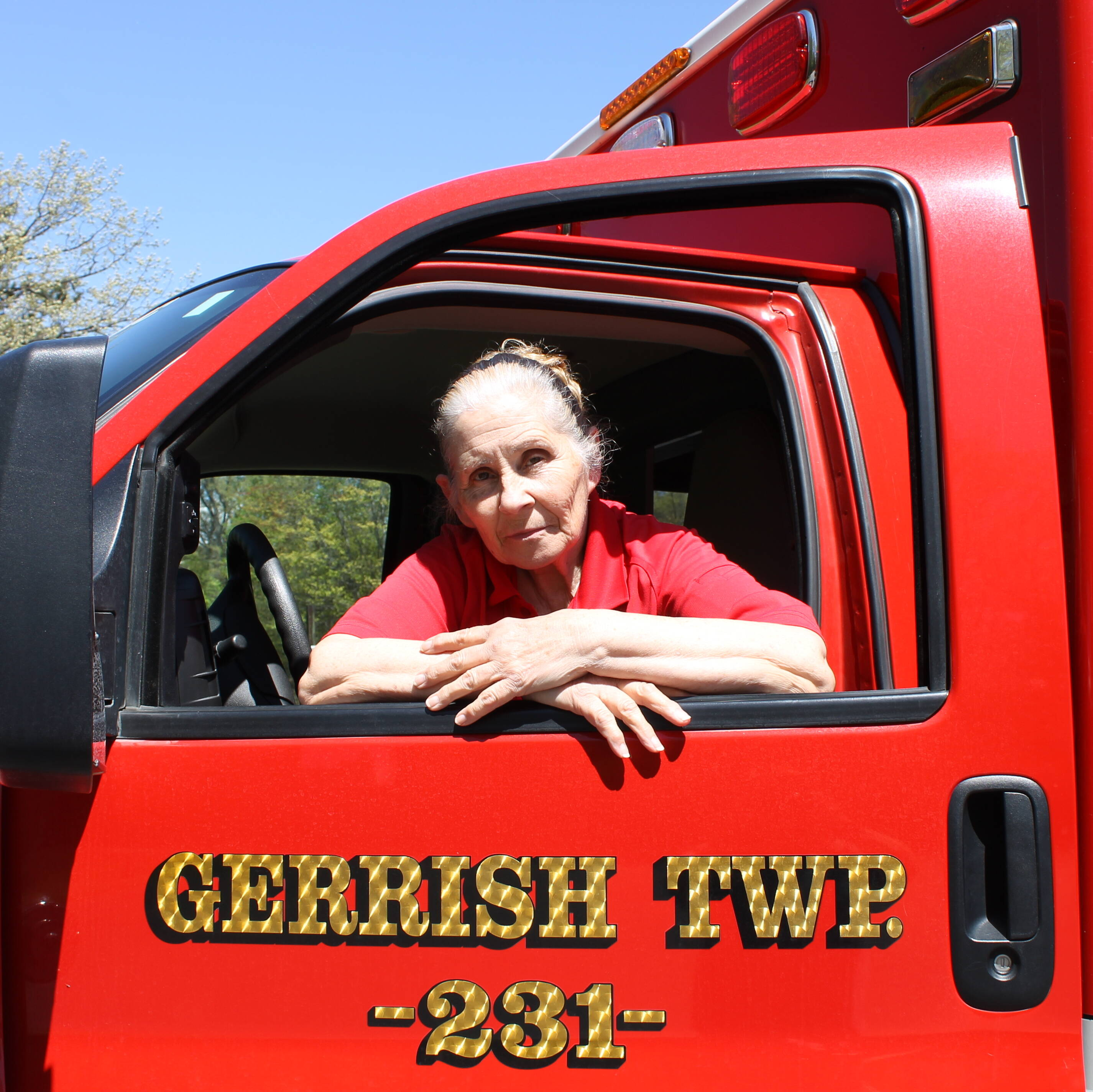 Instructor Coordinator Kathy Pardo posing in the driver-side window of a Gerrish Township fire engine.