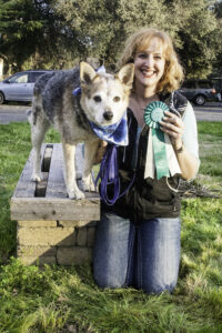 a cattle dog stands on a wooden bench bench and a white woman kneels beside him. Both are facing the camera and the woman holds a prize ribbon and is smiling.