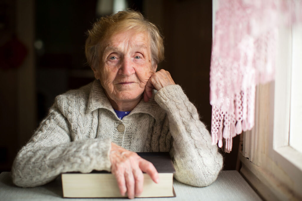 old woman sitting by a window holding a book