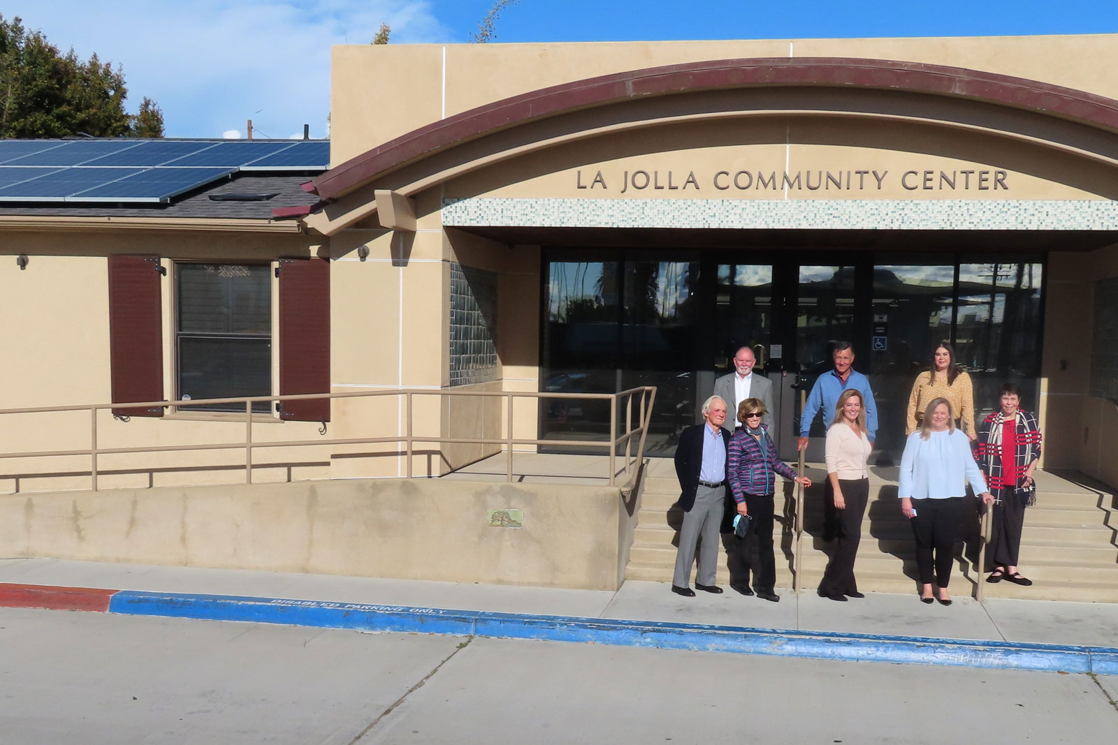The Sahm Family Foundation board of directors stands in front of the La Jolla Community Center with a view of its new rooftop solar panels