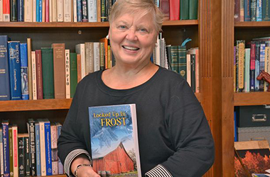 Author Pat Buschette holds her first novel, Locked up in Frost
