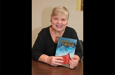 Author Pat Buschette holds her book in her hands