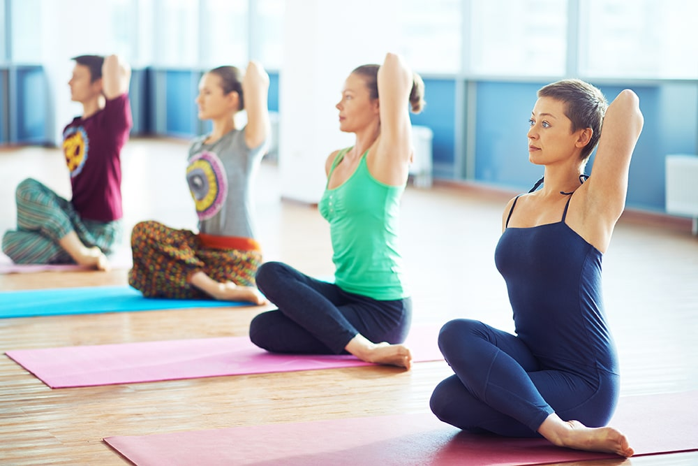 Women and man stretching arms during yoga exercise in gym