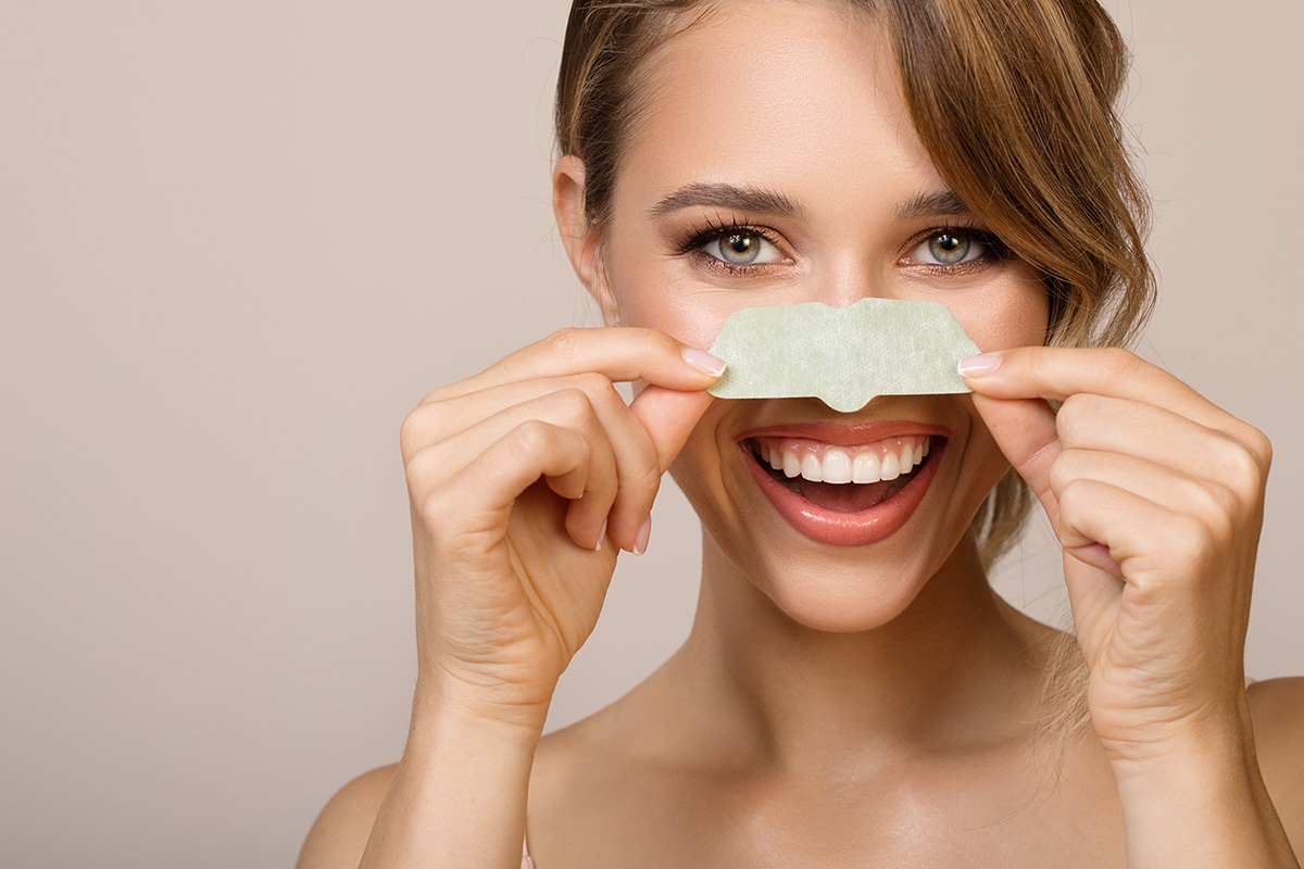 Happy woman using nose mask to remove blackheads