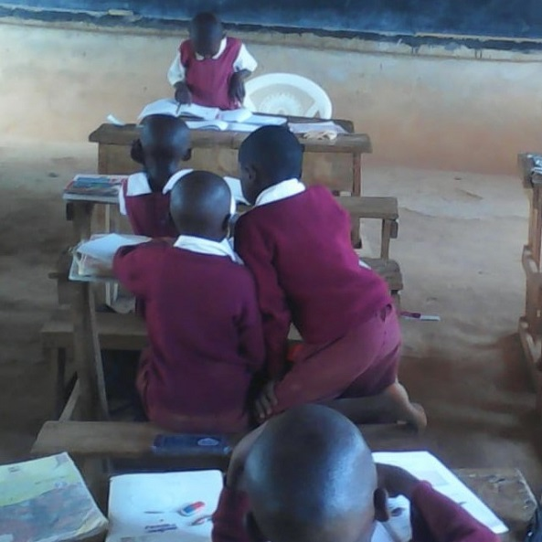 Student at Kwamboo primary, reading for the others during a lesson