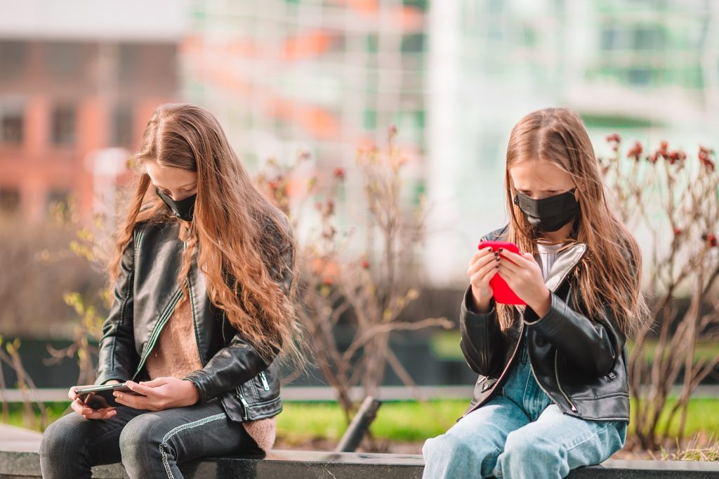 Little girl wearing a mask outdoors for prevent virus and playing smartphone. Protection against Coronavirus and gripp
