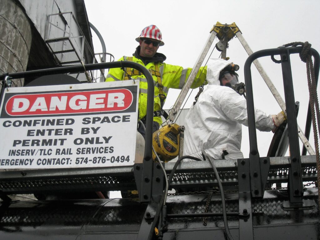 Guys on top of railcar preparing for confined space entry