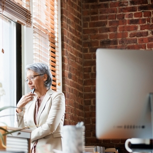 Hispanic businesswoman looking out office window