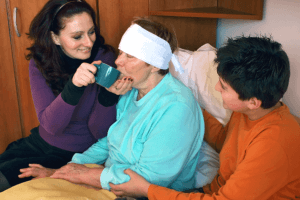 caregiver assisting her patient to drink