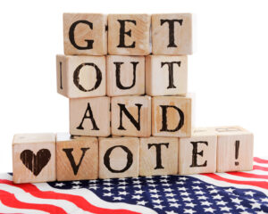 "Rustic alphabet blocks arranged to say, ""Get out and Vote!"" sitting on a bed of stars and stripes."