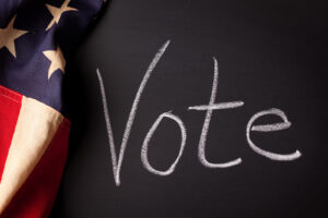 "The word ""Vote"" handwritten on a chalkboard with vintage American flag."