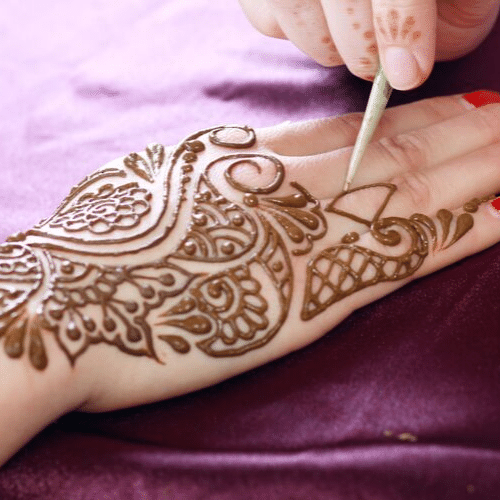 A henna tattoo artist working on someone's hand in Denver