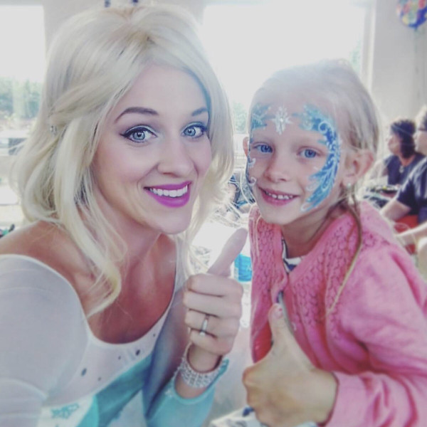 A little girl at a princess party in Denver with a woman dressed in blue.