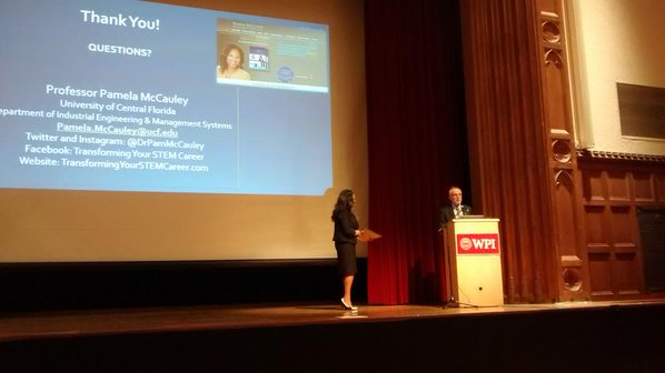 dr pamela mccauley giving a presentation standing on stage next to a man at a podium