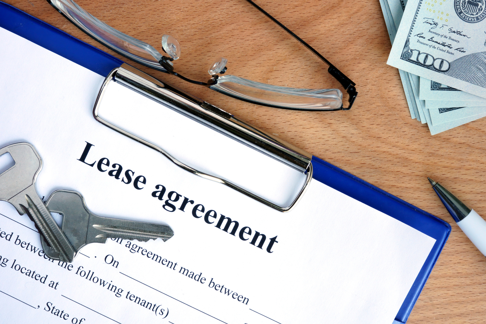 Lease agreement document with money on a wood background
