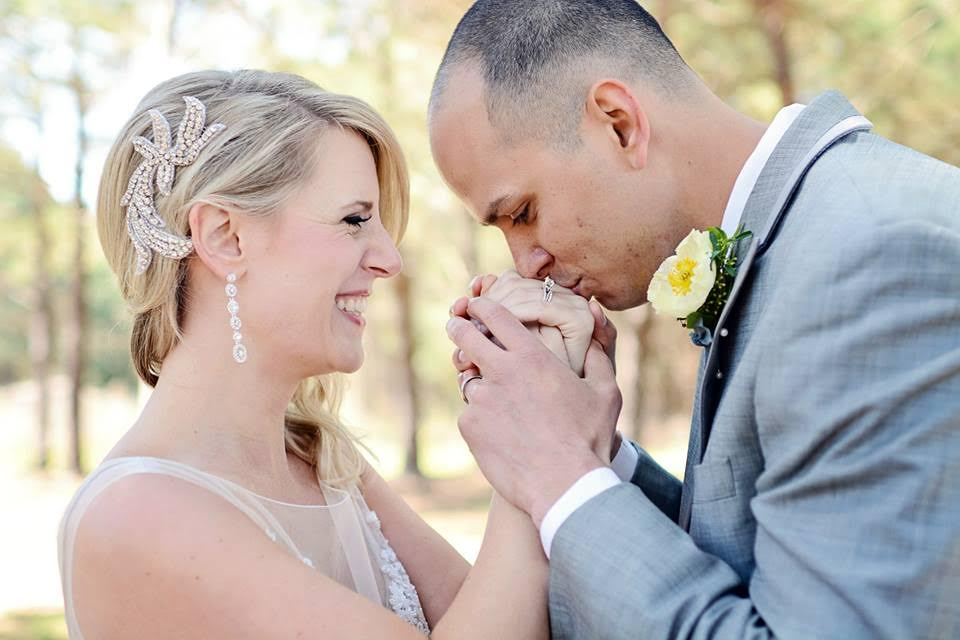 A groom, dapper in his gray suit and yellow boutonnierre, kisses the hands of his smiling bride.