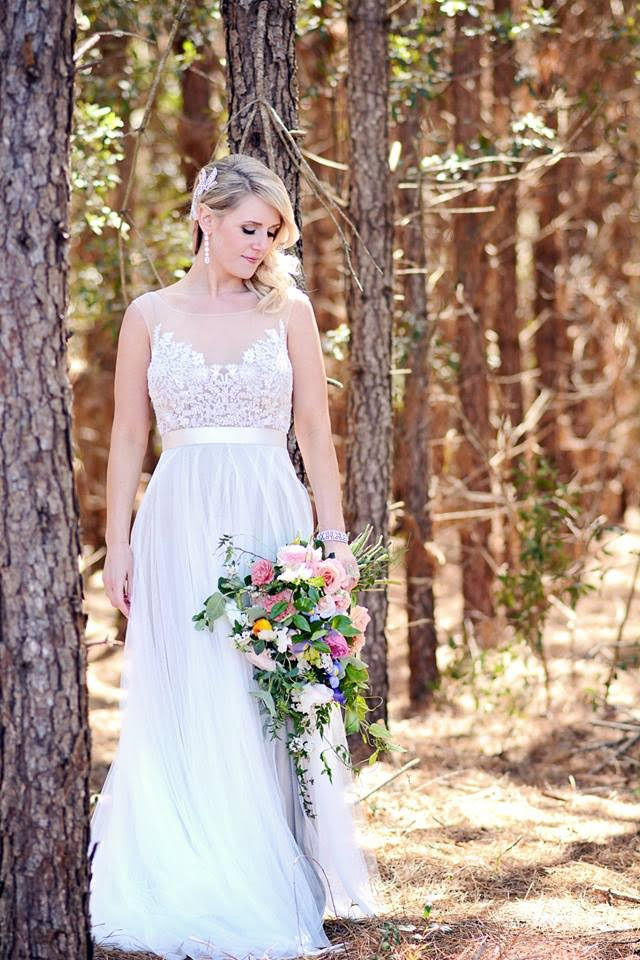 A bride looks down towards her bridal bouquet clutched in her hands as she stands in a grove of winter pines.