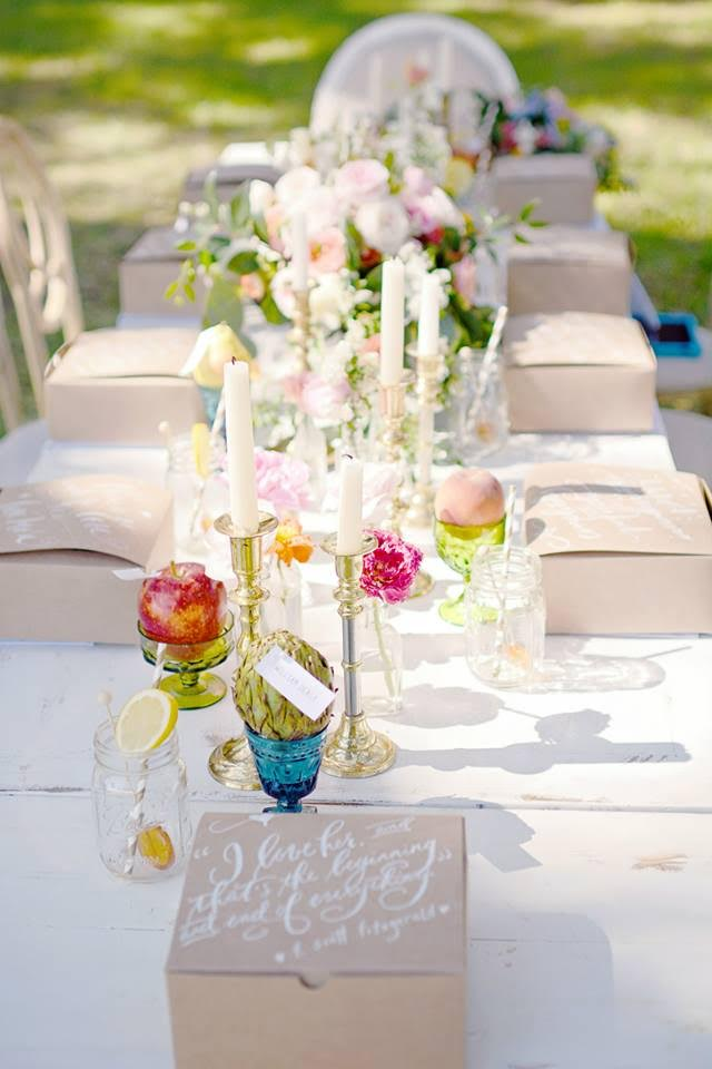Bright florals, colorful glassware, and glamorous candles create a beautiful tablescape for an outdoor wedding.