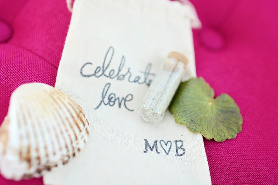 "A bag embroidered with ""celebrate love"" lies on a fuchsia pink couch with a vial of sand and a shell to commemorate the bride and groom's beach wedding."