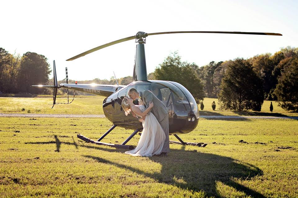 A groom dips his bride and kisses her in front of the helicopter that has come to whisk them away for their wedding night.