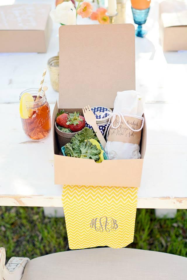 A wrapped sandwich and strawberries fill a craft paper food box that sits on a monogrammed napkin next to a mason jar full of sweet tea.