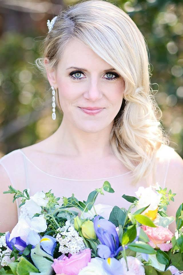 A close-up shot of a lovely blonde bride looking over her colorful bridal bouquet, her long diamond earrings dangling over her shoulder.