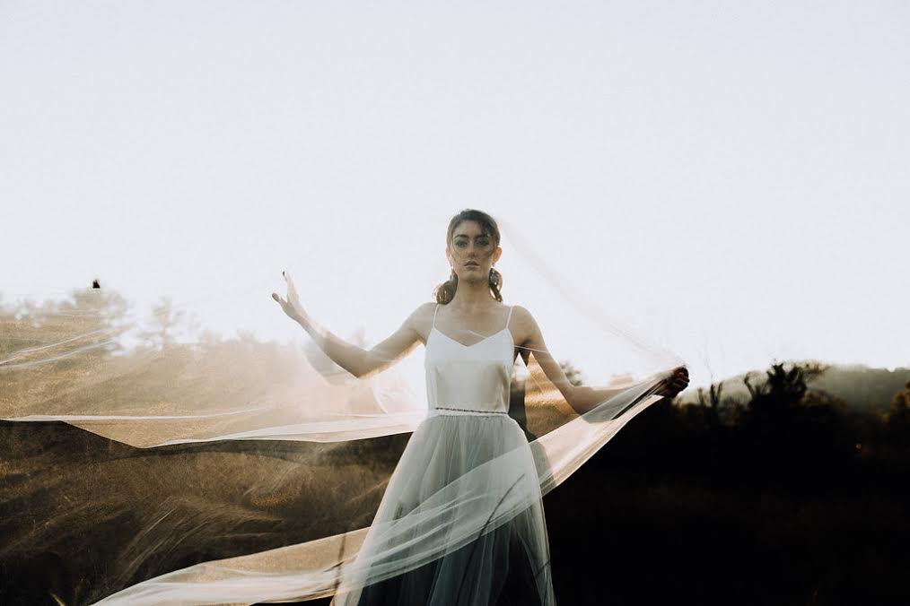 A sweeping veil wraps around a bride dressed in a simple wedding gown from Wildflower Bridal.