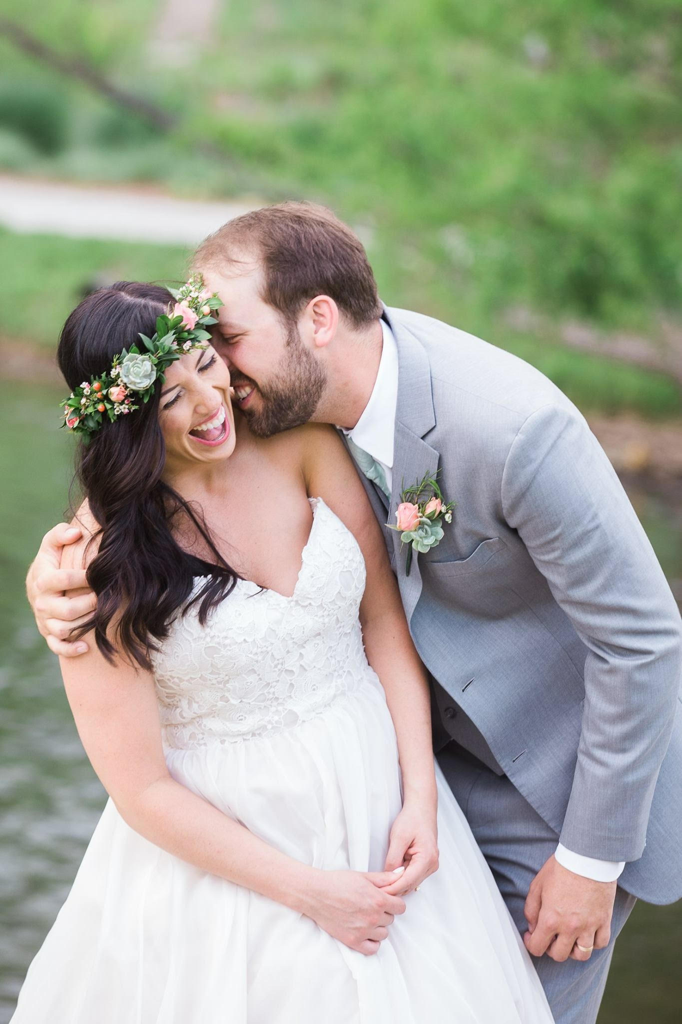 Bride wearing a flower crown over her loosely curled hair style laughs as her groom nuzzles into her ear.