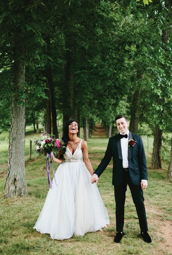 Bride and groom laugh as they hold hands standing outside in a grove of trees.