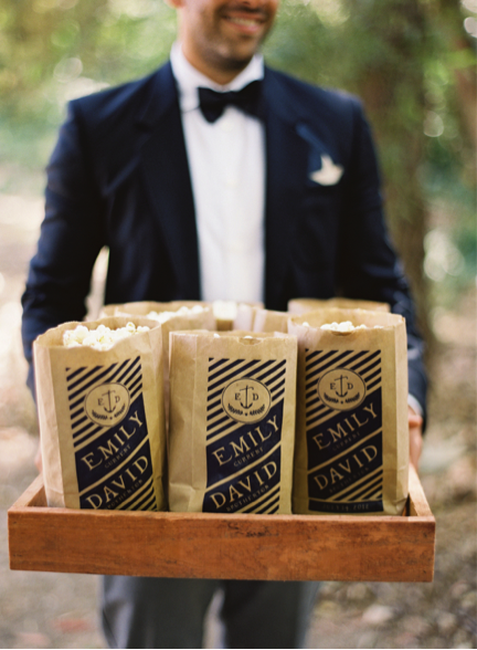 "Groomsman in tux holds wooden tray with paper popcorn bags that read ""Emily and David"""