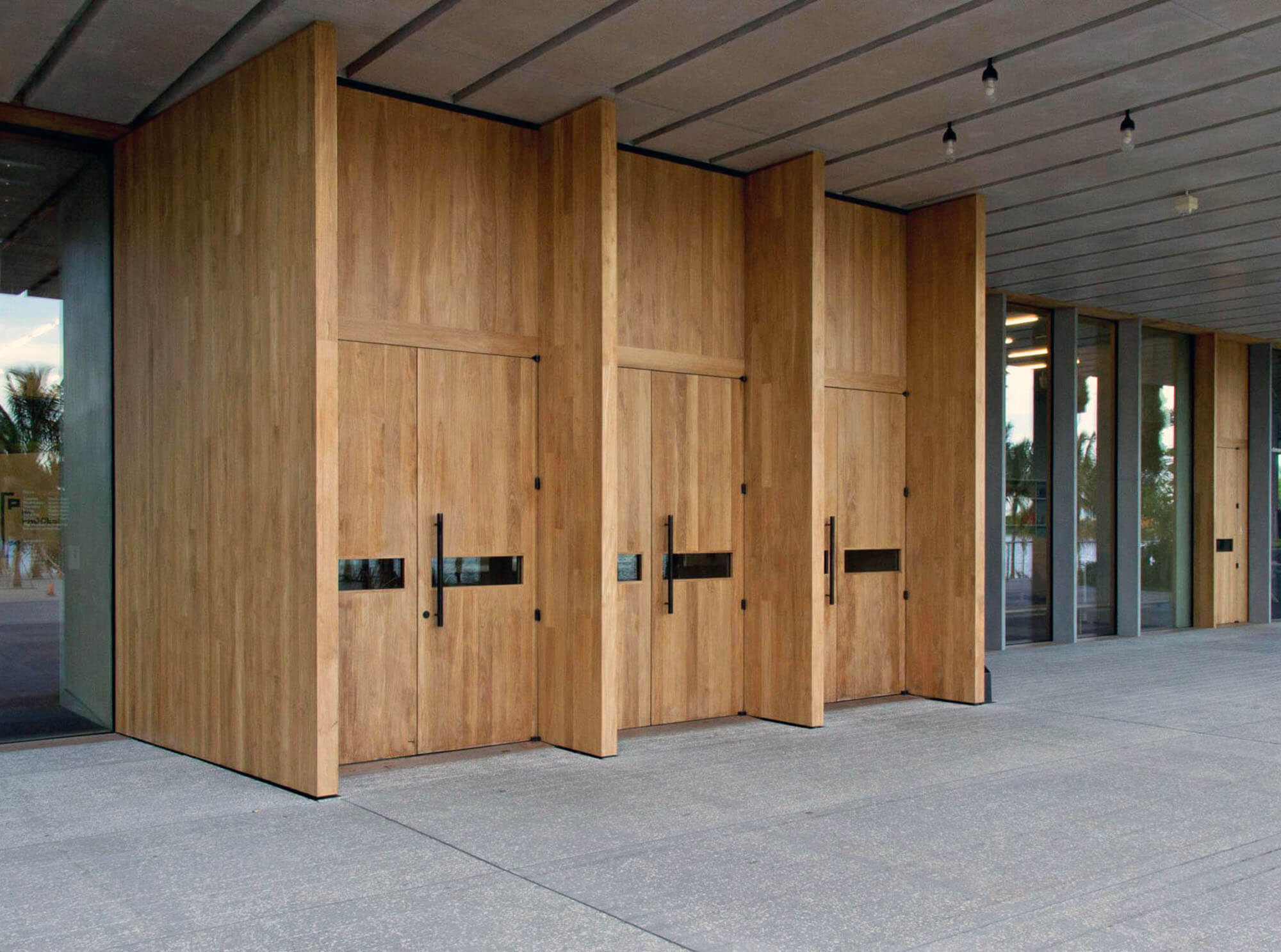 TEAK ENTRY DOORS FRONT ENTRANCE OF THE MIAMI PEREZ ART MUSEUM.