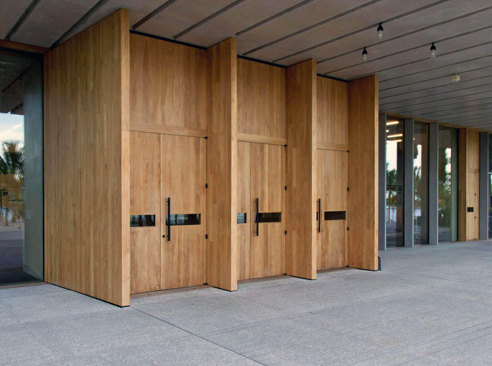 TEAK ENTRY DOORS FRONT ENTRANCE OF THE MIAMI PEREZ ART MUSEUM.