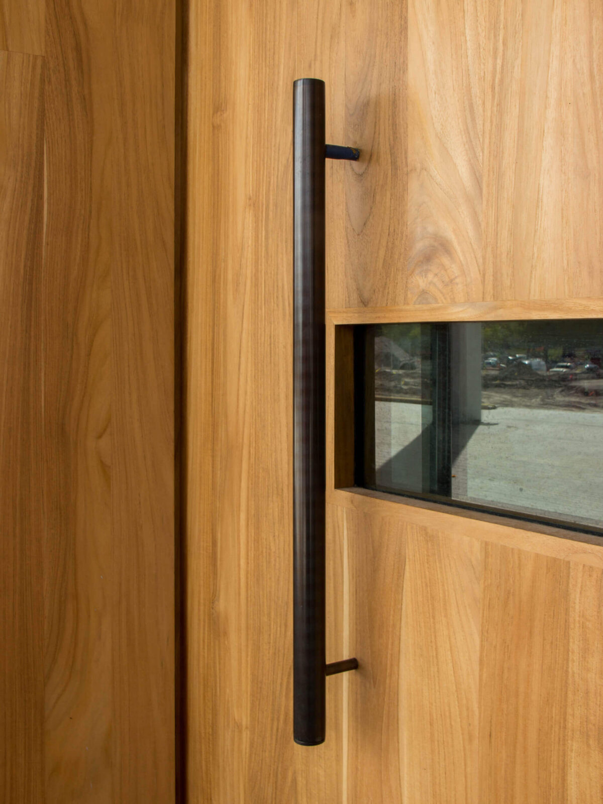 TEAK DOORS. DETAIL OF CUSTOM MANUFACTURED PULL.
